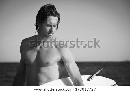 Young handsome man portrait at the sea with surfboard, black and white image.