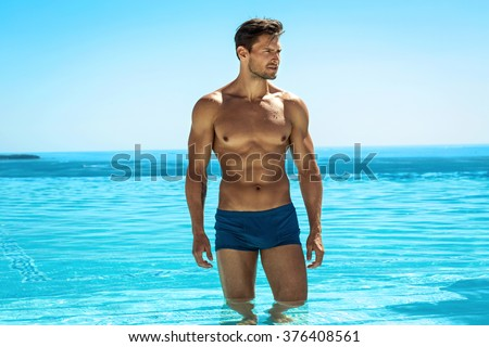 Young handsome man posing in swimming pool - stock photo
