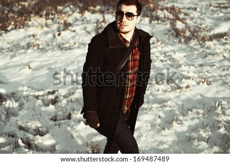 young handsome man posing outdoor in snow field in winter outdoor alone. Smiling well dressed and fashion style cold portrait
