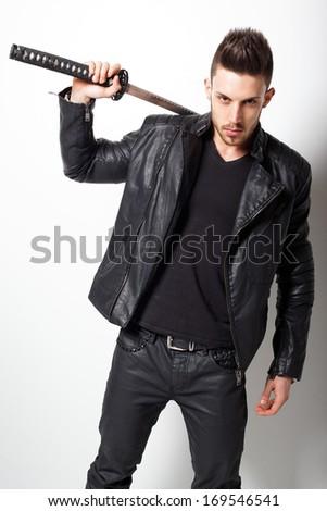 Young handsome man posing with samurai sword. Fashion photo  - stock photo