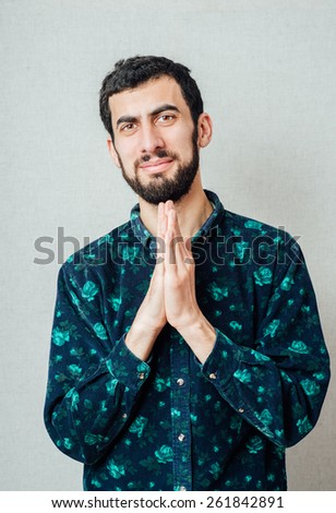 Young handsome man praying hands near your mouth. Gesture. On a gray background - stock photo