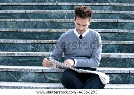 Young handsome man reading newspaper - stock photo