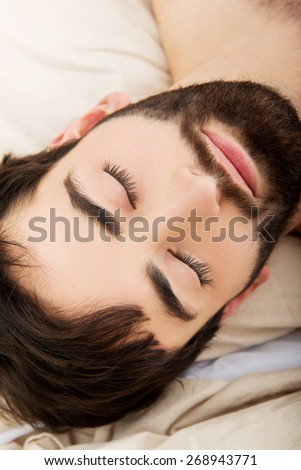 Young handsome man relaxing in bed. - stock photo