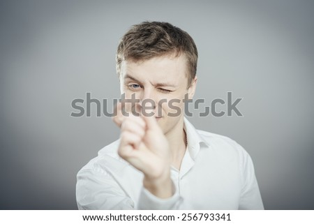 Young handsome man show a little bit. Gesture. On a gray background
