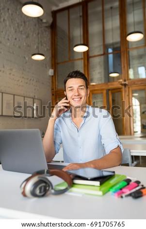young handsome man sitting at table in co-working office, working at laptop, work place, smiling, happy, positive mood, talking on smartphone