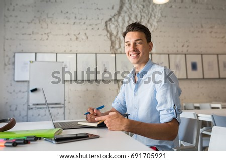 young handsome man sitting at table in co-working office, working at laptop, work place, smiling, happy, positive mood, writing diary book