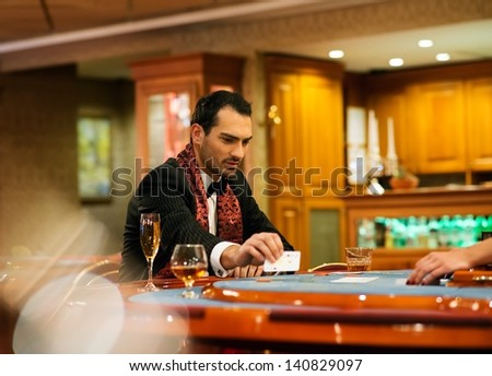 Young handsome man sitting behind poker table with card