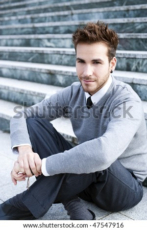 Young handsome man sitting on stairs - stock photo