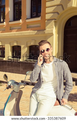 Young handsome man sitting on the motorbike talking on the phone - stock photo