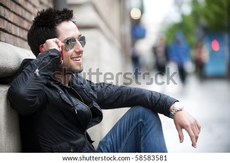Young handsome man sitting on the street speaking on the phone - stock photo