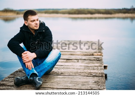 Young handsome man sitting on wooden pier in autumn day, relaxing,  thinking, listening. Casual style - jeans, jacket - stock photo