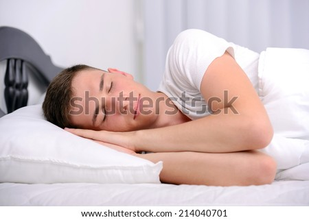 Young, handsome man sleeping in a bed in her bedroom - stock photo