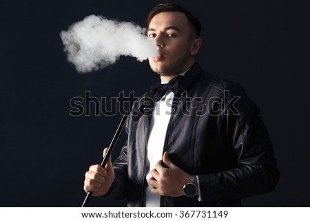 Young, handsome man smoking a hookah. It produces smoke from his mouth. Business style clothing. The pleasure of smoking.