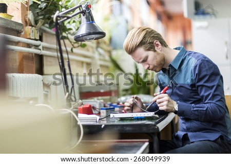 Young handsome man soldering a circuit board and working on fixing hardware - stock photo