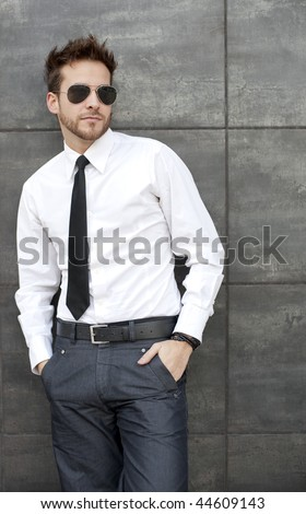 Young handsome man standing against wall with sun glasses and necktie - stock photo