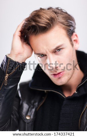 Young handsome man studio portrait captured over light gray background