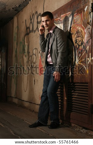 young handsome man talking on cellular phone in tunnel - stock photo
