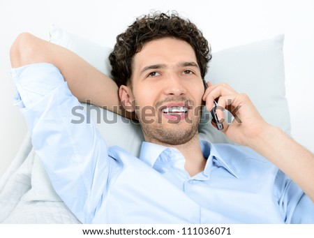 Young handsome man talking on modern mobile phone. Studio shot. - stock photo