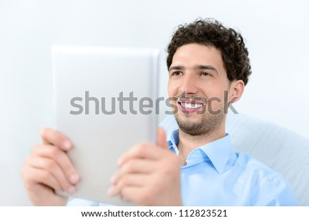 Young handsome man using a modern digital tablet. Studio shot. - stock photo