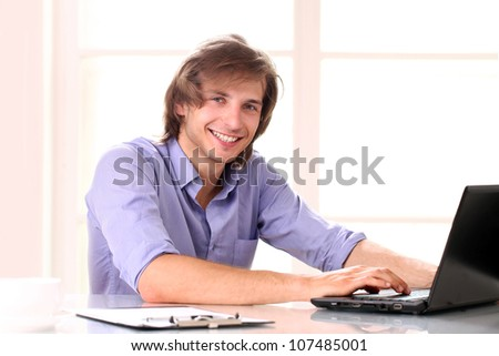 Young handsome man using laptop in his office - stock photo