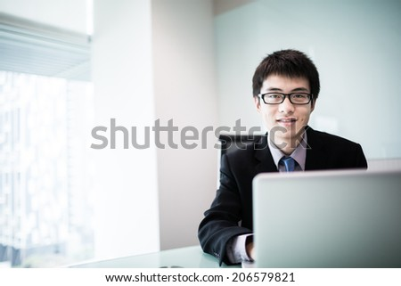 Young handsome man using laptop in his office.Asian - stock photo