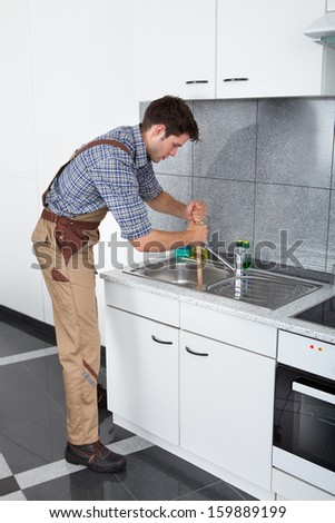 Young Handsome Man Using Plunger In Kitchen Sink - stock photo