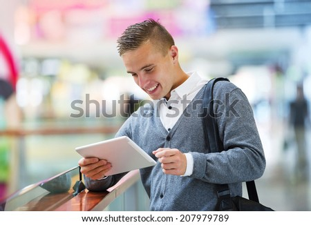 Young handsome man using tablet in shopping mall - stock photo