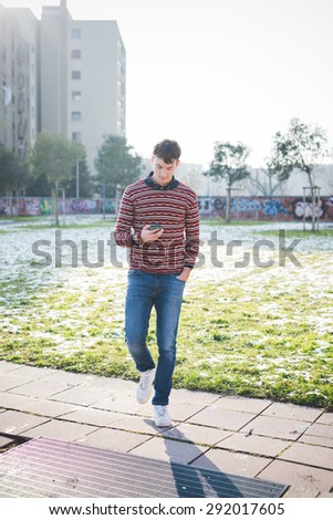 Young handsome man walking on a park in the city while using a smartphone. He is wearing blue jeans and a red striped sweater. - stock photo