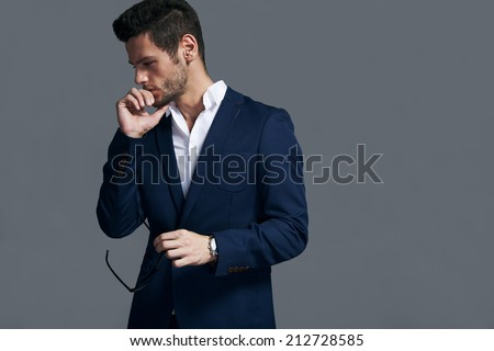 Young handsome man wearing fashion eyeglasses against neutral background with lots of copy space - stock photo