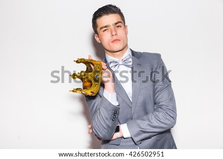 young handsome man wearing with crown in hands suit  looking at camera while standing against white background - stock photo