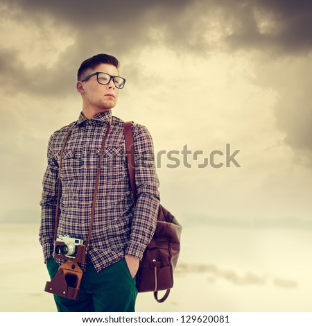 young, handsome man with a camera, dressed in the style of hipster - stock photo