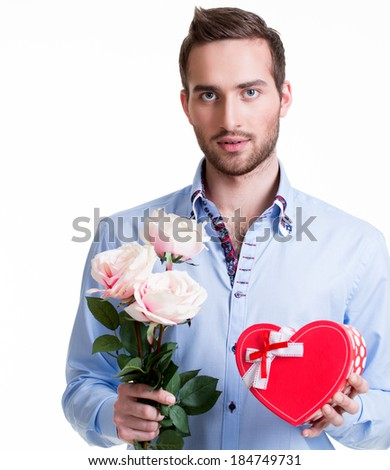Young handsome man with a pink roses and a gift - isolated on white. - stock photo