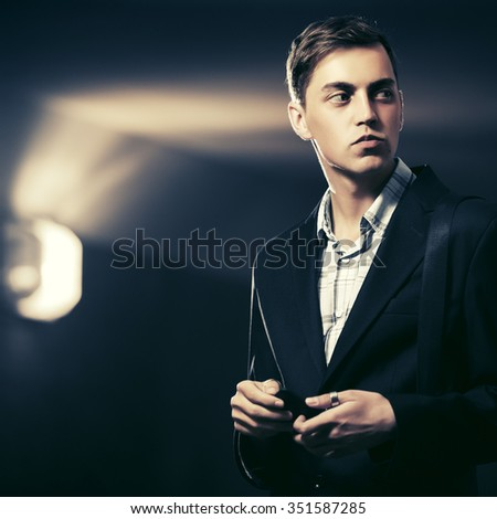 Young handsome man with a smart phone standing at the wall - stock photo