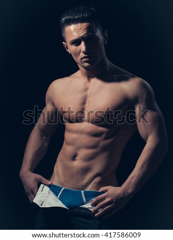 young handsome man with bare torso and sexy muscular body in trausers in studio