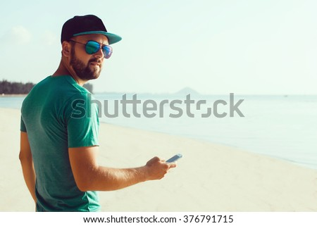 young handsome man with beard and mustache in baseball cap, with a smartphone in hand, hipster style, outdoor portrait, close up,posing on the beach in a t-shirt and denim shorts, the bearded - stock photo