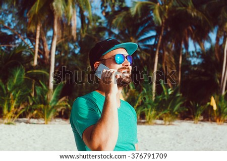 young handsome man with beard and mustache in baseball cap, with a smartphone in his hand talking on the phone, hipster style, outdoor portrait, close up - stock photo