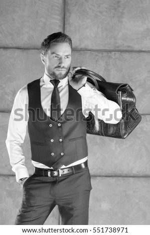 Young handsome man with beard, mustache traveling, wearing white shirt, blue vest, shoulder carrying genuine brown leather bag, standing near grey wall. Studio portrait. Black and white