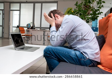 Young handsome man with computer in the office. Thinking over task in programming. Tired - stock photo