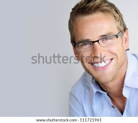 Young handsome man with great smile wearing fashion eyeglasses against neutral background with lots of copy space - stock photo