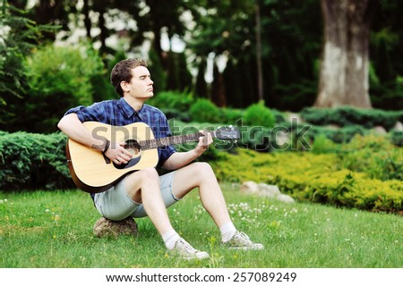 Young handsome man with guitar outdoor  - stock photo