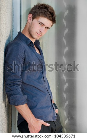 Young handsome man with hands in pockets portrait - stock photo