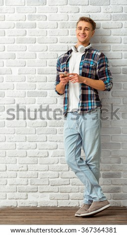 Young handsome man with headphones and smartphone posing against the backdrop of a brick wall - stock photo
