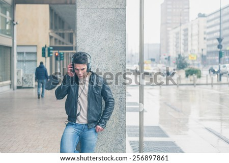 Young handsome man with headphones listening to music in the city streets