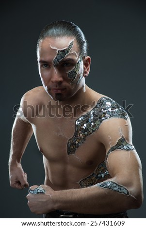 Young handsome man with  mosaic body art, standing in front of black background: body-art project