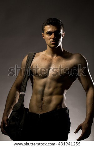 Young handsome man with muscular body bare torso posing in studio with training bag on chest on grey background