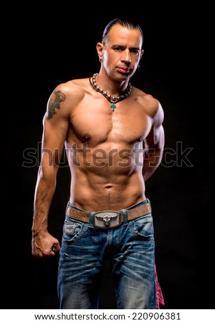 Young handsome man with naked torso on a dark background