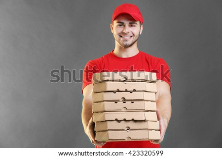 Young handsome man with pizza on grey background - stock photo