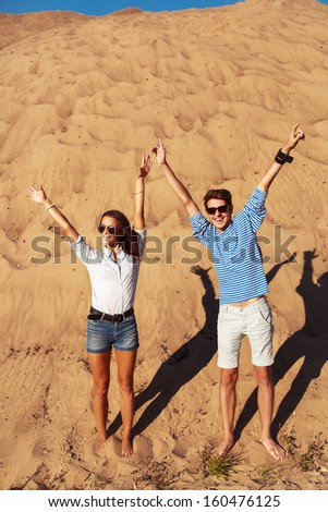 Young handsome man with pretty brunette girlfriend having fun and putting hands in the air together in summer - stock photo