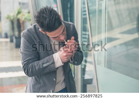 Young handsome man with short hair smoking a cigarette in the city streets - stock photo