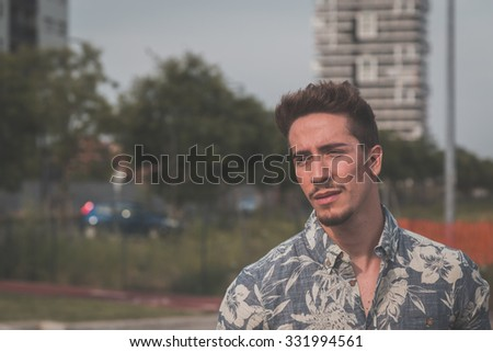 Young handsome man with short hair wearing a short sleeve shirt and posing in an urban context - stock photo